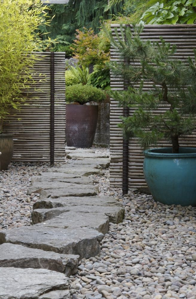 pebbles and a large rough stone path on top match potted plants and screens
