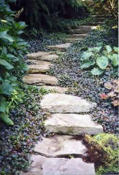 a rough stone path with catchy dark foliage around that accent it with its dark shade