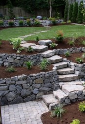 a stone garden path with stone walls around and several flower boxes with various greenery