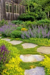 a rough stone garden path with a large space in between each piece and moss growing for a natural feel