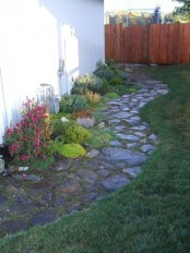 a garden stone path with moss in between and bright blooms growing next to it