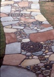 a bold and unique garden path of muted color stones and pebbles that form floral patterns