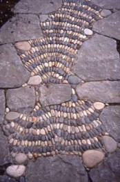 a stone and pebble garden path with pebbles forming some patterns looks cool and bold