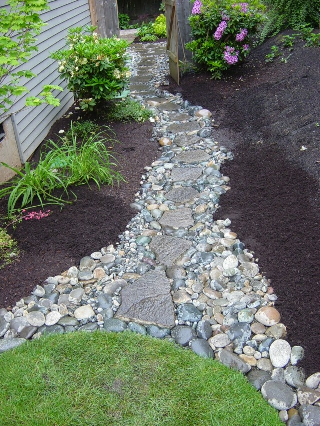 a pebble and rock garden path like this one will add a natural feel to the garden and make it bolder