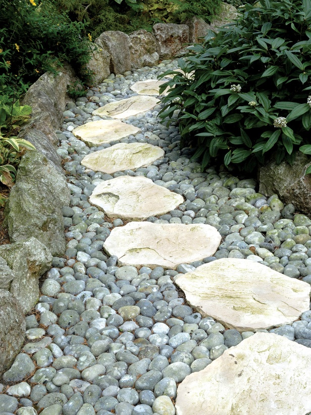 grey pebbles and rough stones and rocks that create a border of the path, a natural and fresh look for every garden