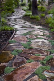 a rough stone garden path with moss and accurate borders for a natural yet manicured feel