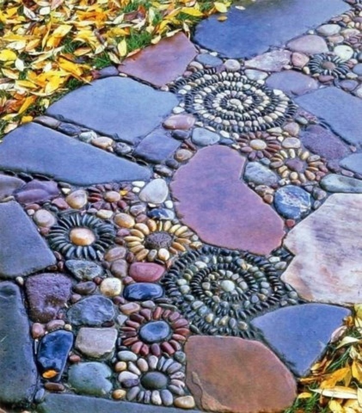 a bold garden path with muted color stones and pebbles that form floral and swirl patterns looks very eye catching