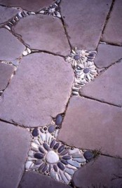 a rough stone pathway with small pebble flower inserts in it that make it bolder and cuter