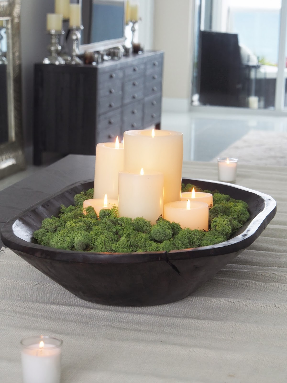 a dark stained dough bowl with moss and pillar candles is a cool centerpiece with a fresh feel