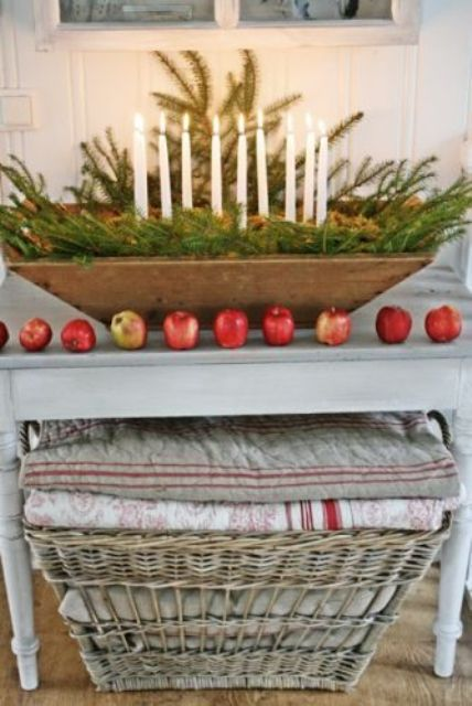 a Christmas centerpiece of a dough bowl, fir branches and thin candles plus apples along it