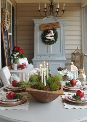 an elegant Christmas centerpiece of a dough bowl, greenery, vine balls and candles