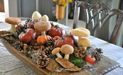 a wild fall centerpiece of a dough bowl, pinecones, moss, faux pumpkins and mushrooms plus some hay