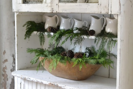 a dough bowl with fir branches and pinecones is a nice winter decoration