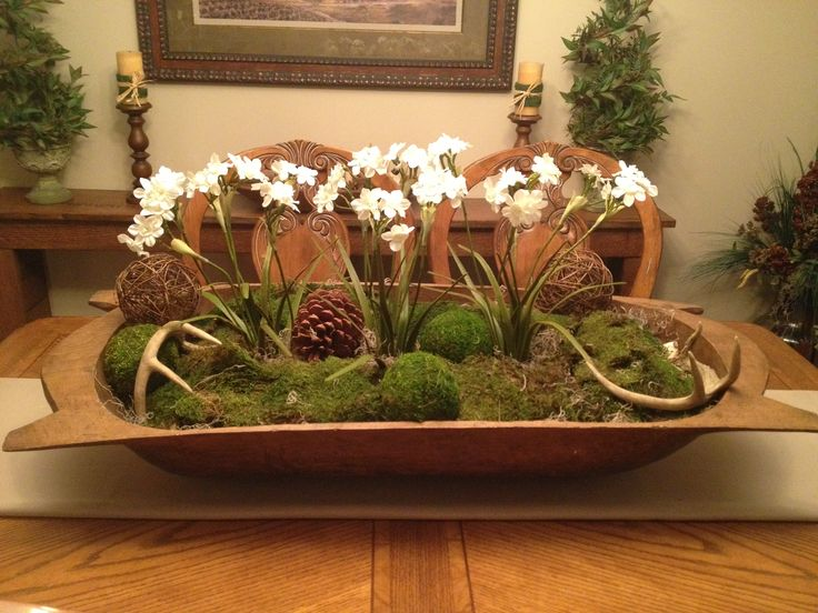 a dough bowl with moss, vine balls, antlers and spring bulbs for a winter decoration or centerpiece