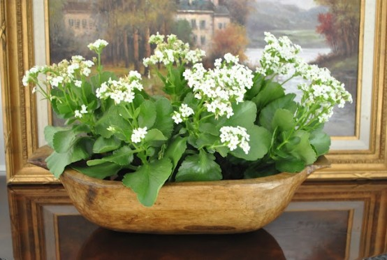 a vintage dough bowl as a planter with white blooms is a cool rustic or farmhouse idea