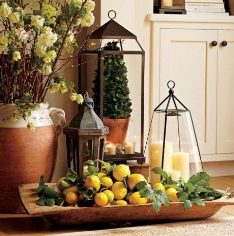 a vintage rustic decoration of a dough bowl, lemons, greenery and a couple of candle lanterns