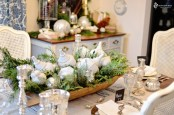 a winter centerpiece of a dough bowl, ferns and fir branches and white vintage Chhristmas ornaments