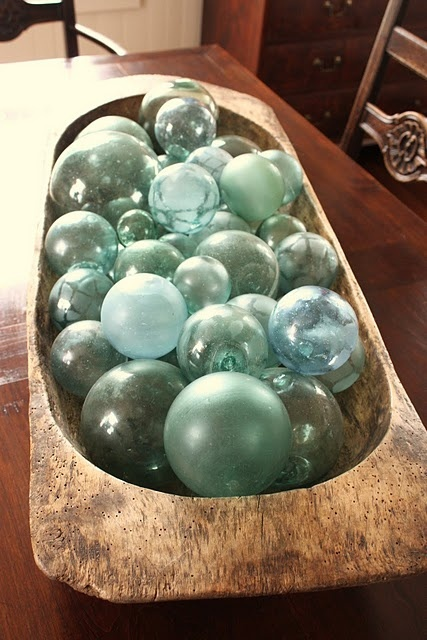 a large dough bowl with blue glass floats is a cool centerpiece for a coastal home