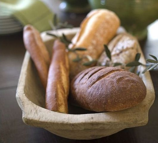 a dough bowl with fresh bread is an edible centerpiece idea -what can be more natural than storing bread in a dough bowl
