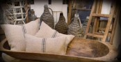 a dough bowl used for storing pillows is a rustic touch to your living room