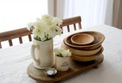 small wooden dough bowls and some blooms can make up a stylish rustic centerpiece
