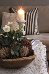 a simple and cute centerpiece with large pinecones and white blooms
