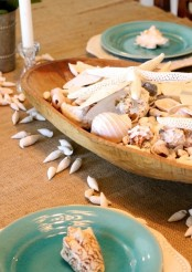 a dough bowl with seashells and starfish is a simple and stylish centerpiece for a coastal home