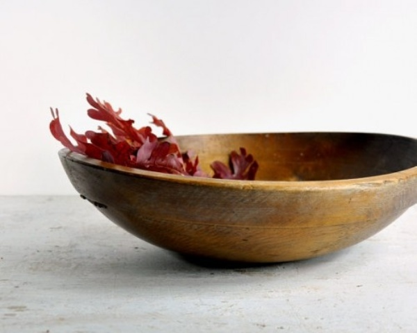 a dough bowl with some burgundy fall leaves is a minimal fall decoration