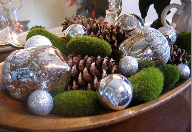 a dough bowl with moss balls, mercury glass Christmas ornaments and large pinecones