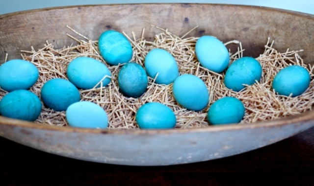 an Easter centerpiece of a whitewashed dough bowl, hay and blue Easter eggs