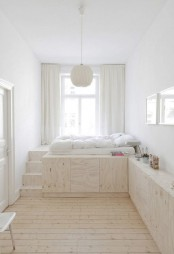 a modern airy bedroom with a raised platform with steps that hides lots of storage units inside