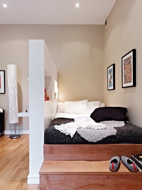 a platform bed with steps is a comfy space-saving solution separated with a wall with niche from the rest of the space