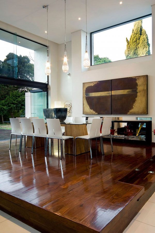 a polished and rich stained wooden platform highlights the dining space and separates it fromt he rest of the layout