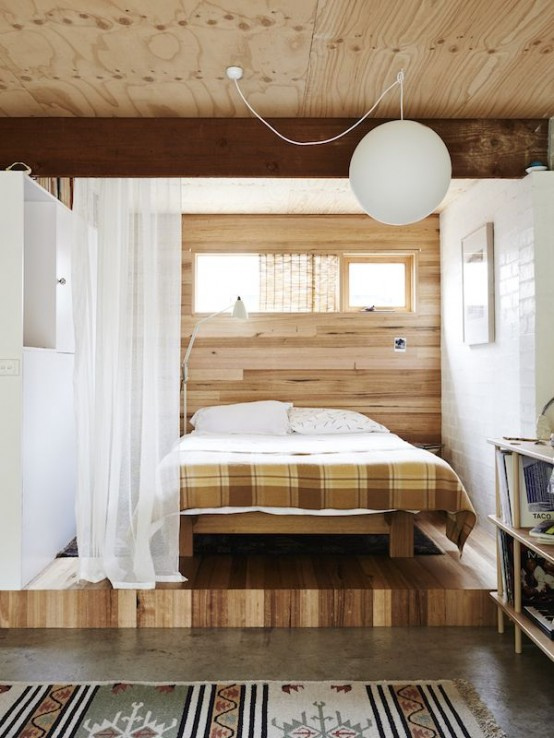 a plywood platform and a matching headboard wall highlight the bedroom space