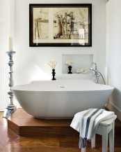 a raised platform highlights the bathtub in the bathroom making this space an oasis