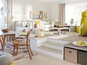 the living space is highlighted with a raised platform with boxes for storage and separated from the dining space