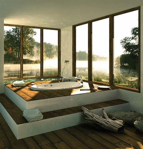 a stepped platform with a sunken tub by the windows makes it a real oasis of relaxation