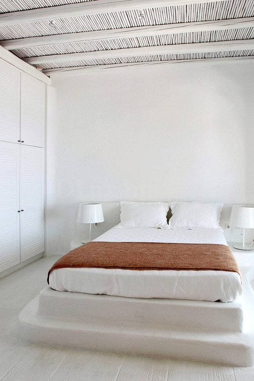 a stepped platform instead of a usual bed is a cool solution for an island bedroom