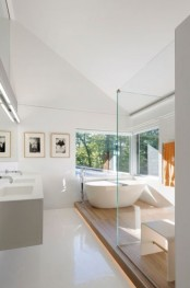 a plywood platform with a tub and a shower to highlight this zone and divide it from the sink space