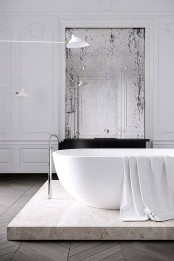 a stone platform makes the sophisticated bathroom even more gorgeous and highlights the bathtub