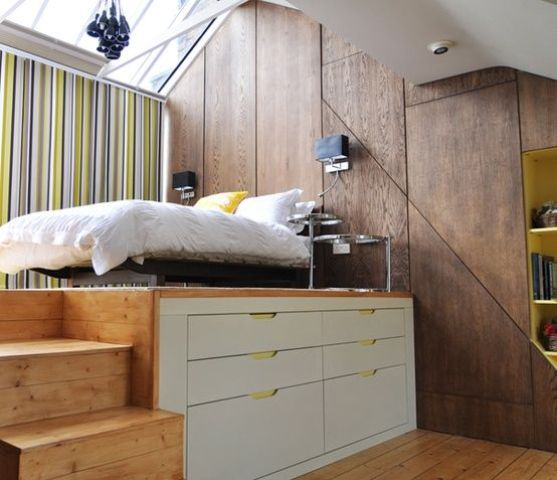 a raised wooden platform with drawers for storage to divide sleeping space and the rest of the apartment