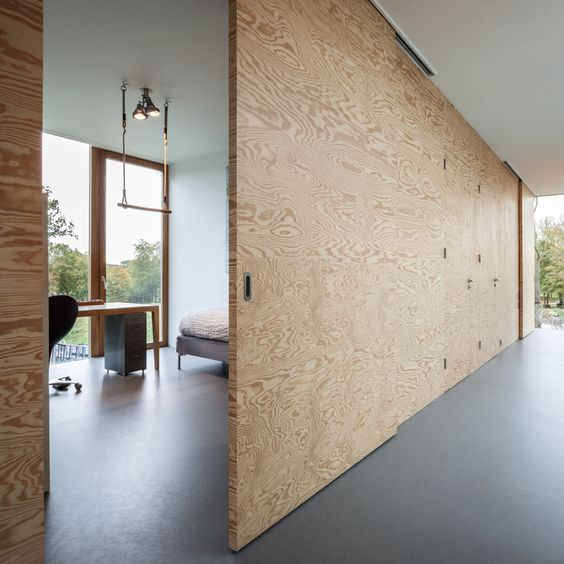 a large plywood sliding door matches a minimalist space and makes it cooler