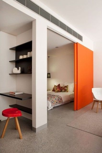 a bright orange sliding door adds color to the space and saves it