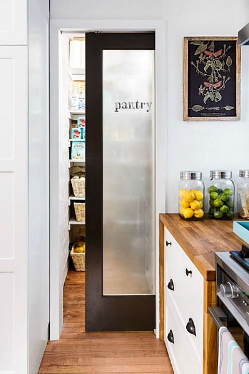 a frosted glass sliding door with dark framing and a word that marks the space behind it - a pantry