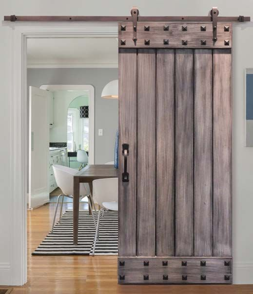 a rustic wooden sliding door with studs is a cool idea for a cozy yet rock touch