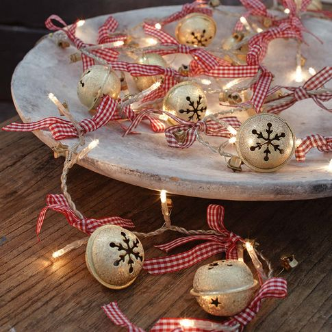 a porcelain tray with lights and Christmas bells with plaid ribbons is a very cool and cozy modern Christmas decor idea