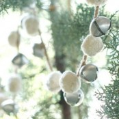 a garland of silver bells and white pompoms can be used on your Christmas tree or someewhere in your home for a chic holiday feel