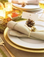 a place setting with a gold charger, a white plate, a neutral napkin with a pinecone and a bell is very chic and Christmassy