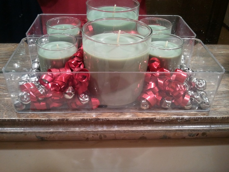 a clear tray with silver bells and green candles in glasses is a cool Christmassy decoration to rock