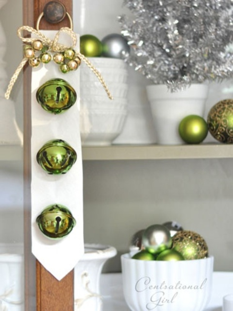 a white tie with green bells and mini ornaments plus a bow can be hung on doors of all kinds to bring a holiday feel to them